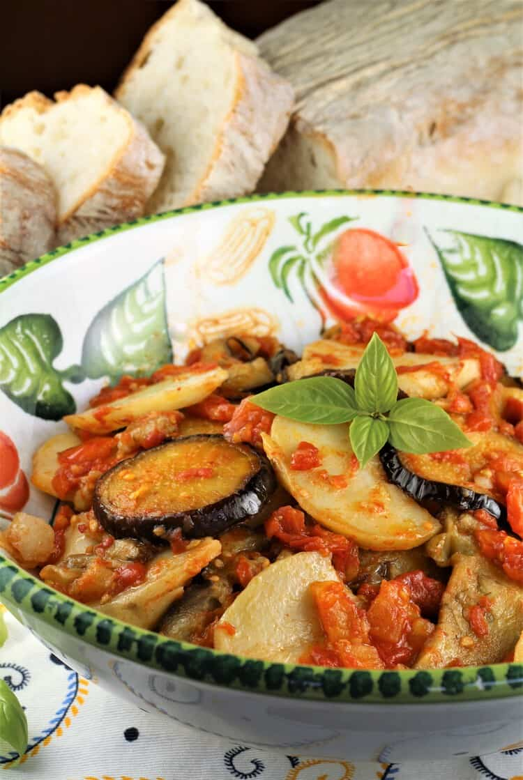 bowl of eggplant, potatoes and tomato sauce with bread in background