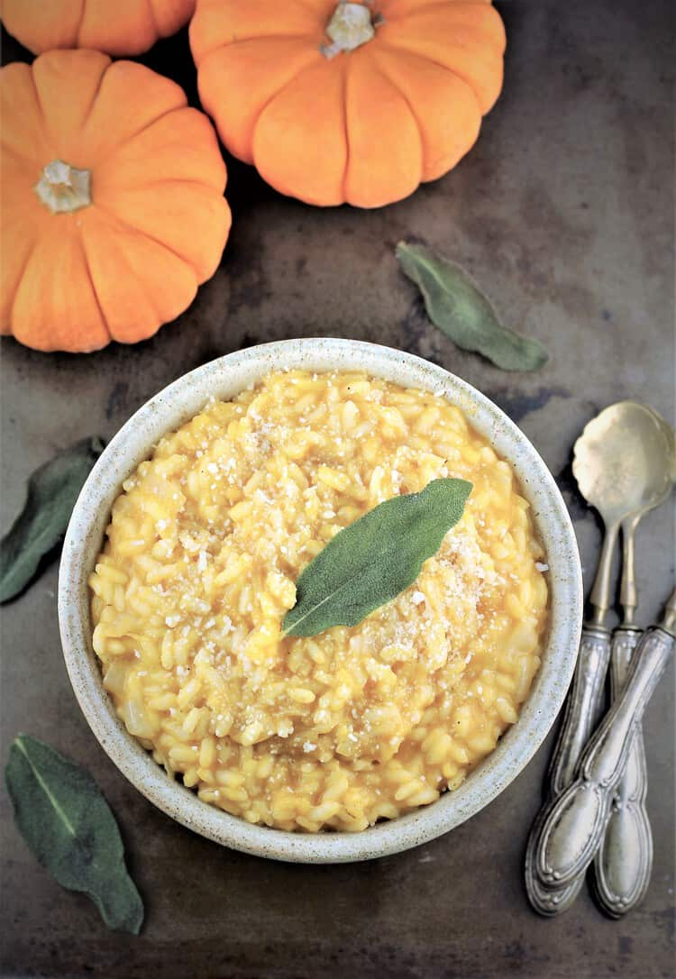 bowl of pumpkin risotto with crispy sage leaf on top and mini pumpkins and spoons on side