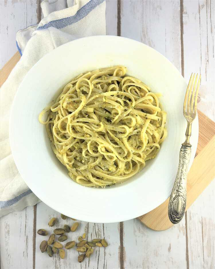 bowl of linguine with pistachio pesto and fork on side