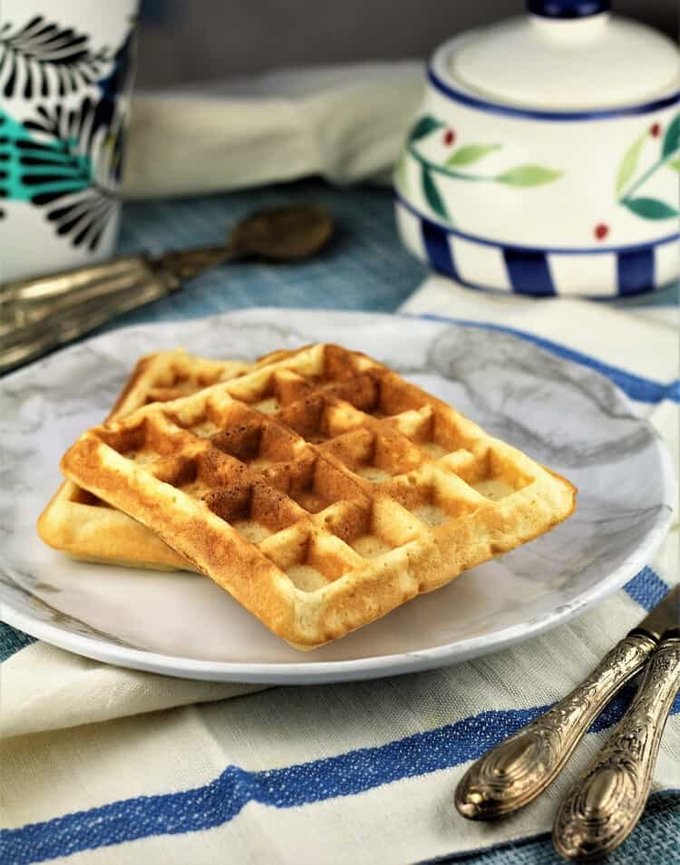 plate with 2 waffles next to cutlery and sugar bowl