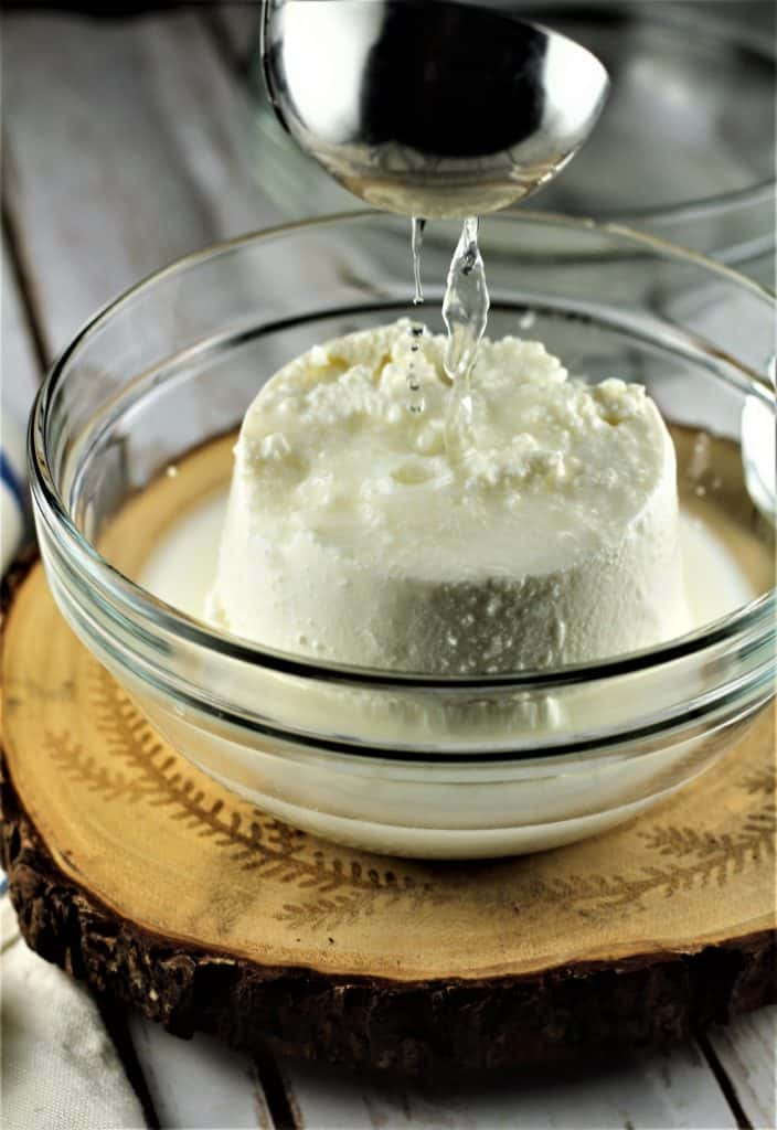 ricotta in a glass bowl with pasta water being ladled over it