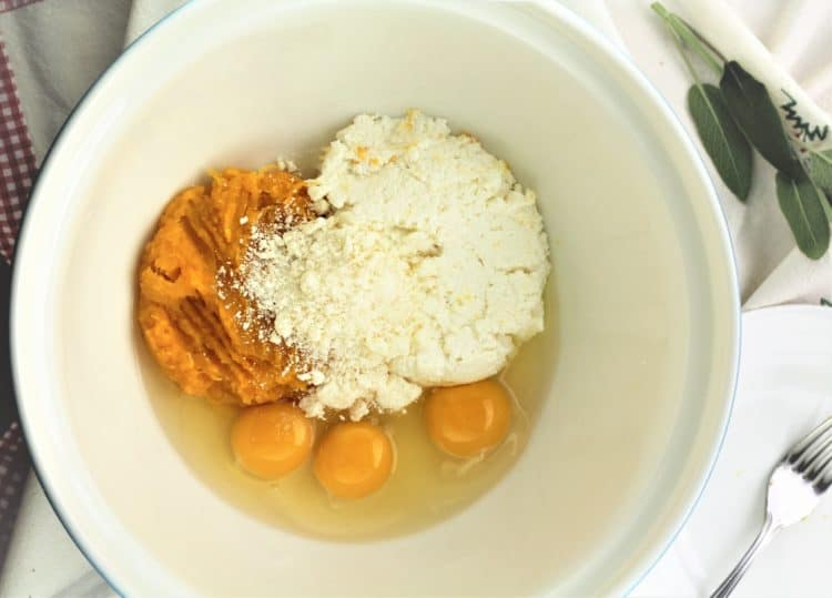 bowl with pumpkin, ricotta, parmigiano and eggs with fork and sage leaves on the side