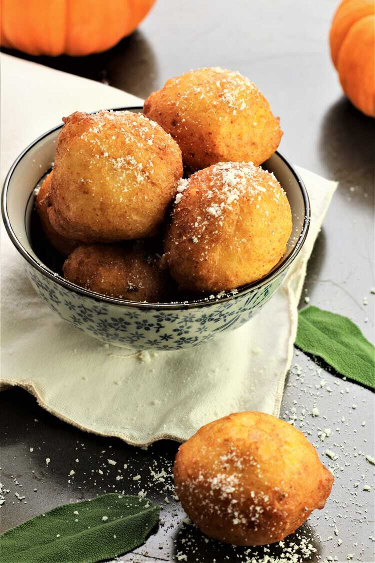 bowl of savory pupmpkin ricotta fritters with mini pumpkins in background