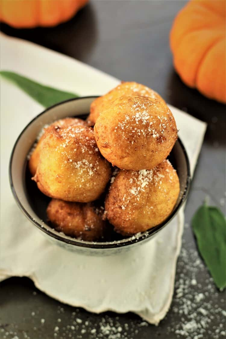 overhead photo pf bowl of pumpkin ricotta fritters with sage leaves and pumpkins behind it