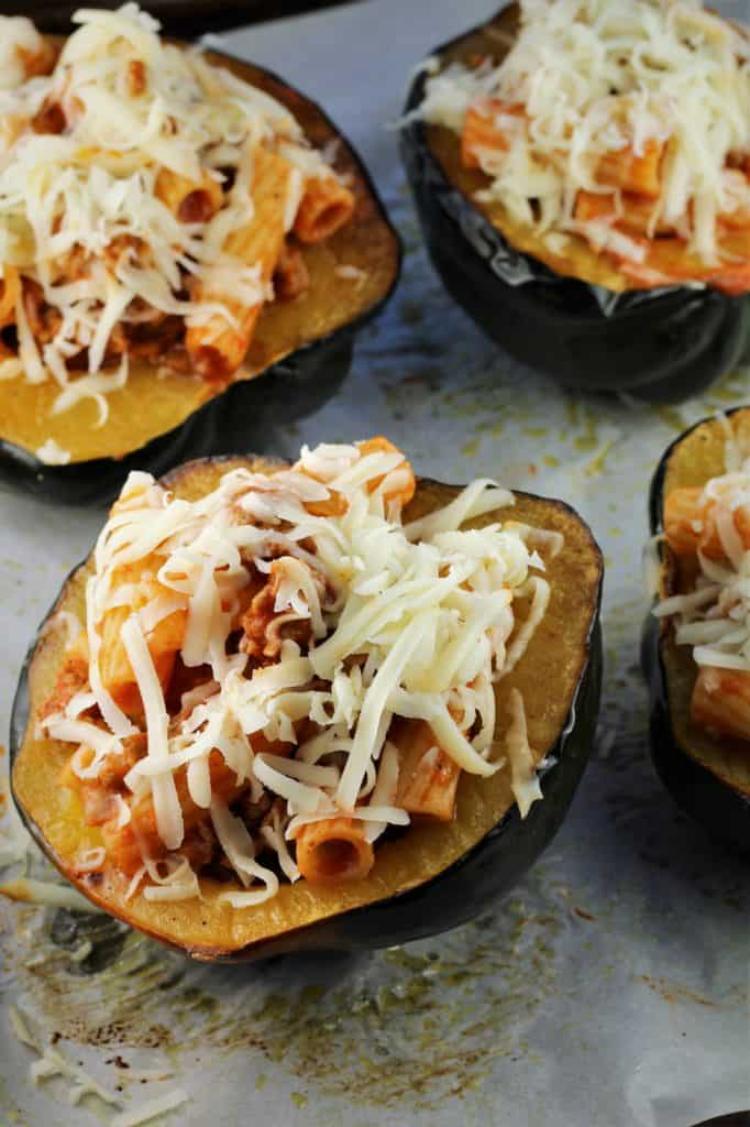 4 acorn squash halves filled with pasta and mozzarella on baking sheet