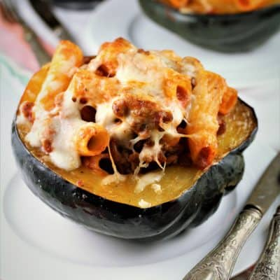 Sausage and Pasta Stuffed Acorn Squash on a plate with utensils on side