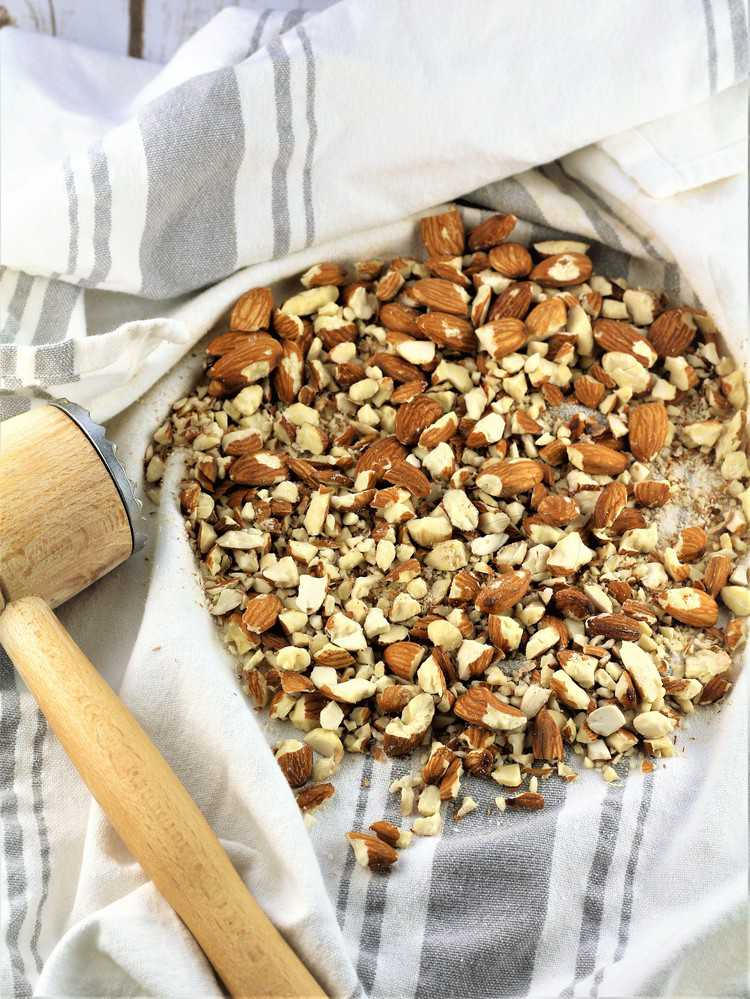 chopped almonds on dish towel with meat mallet on side