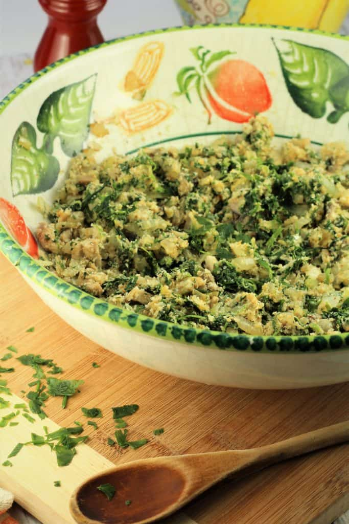 bowl with spinach and mushroom filling on a wooden board with wooden spoon in foreground