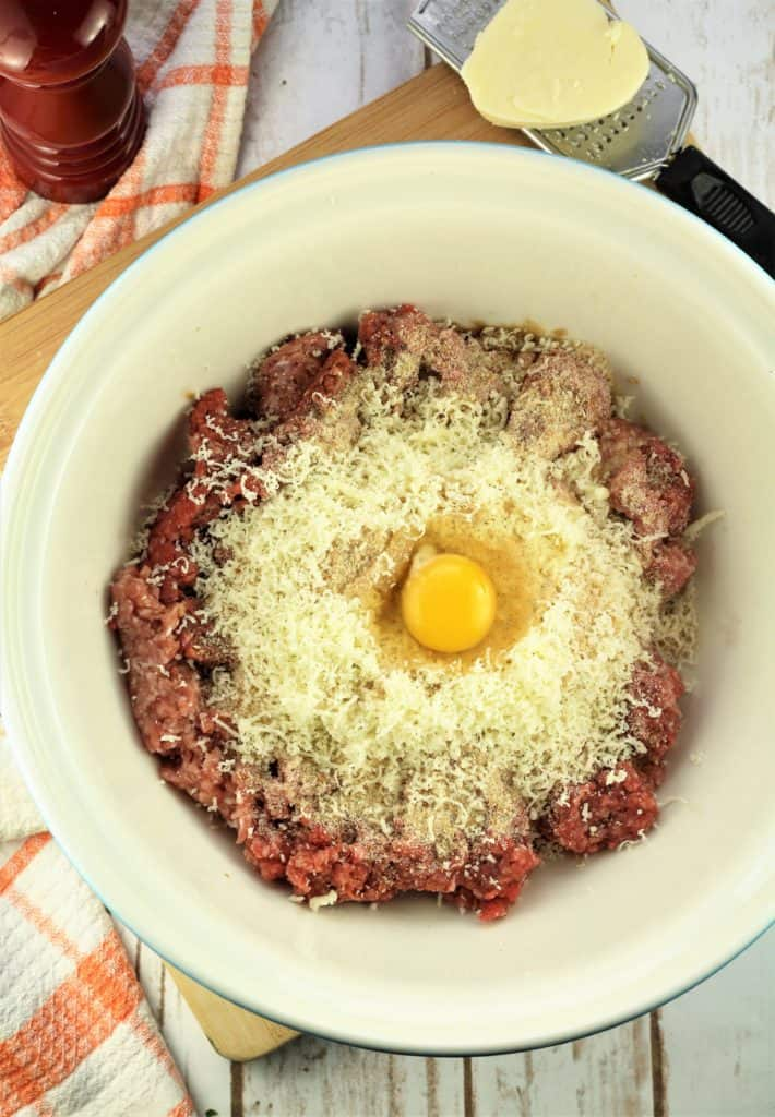 large mixing bowl with ground meat, cheese, breadcrumbs and egg with cheese on grater and pepper mill