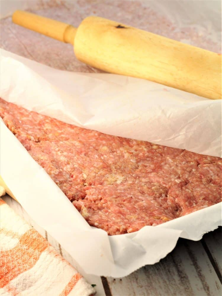 ground meat spread on a baking sheet covered in parchment paper with rolling pin