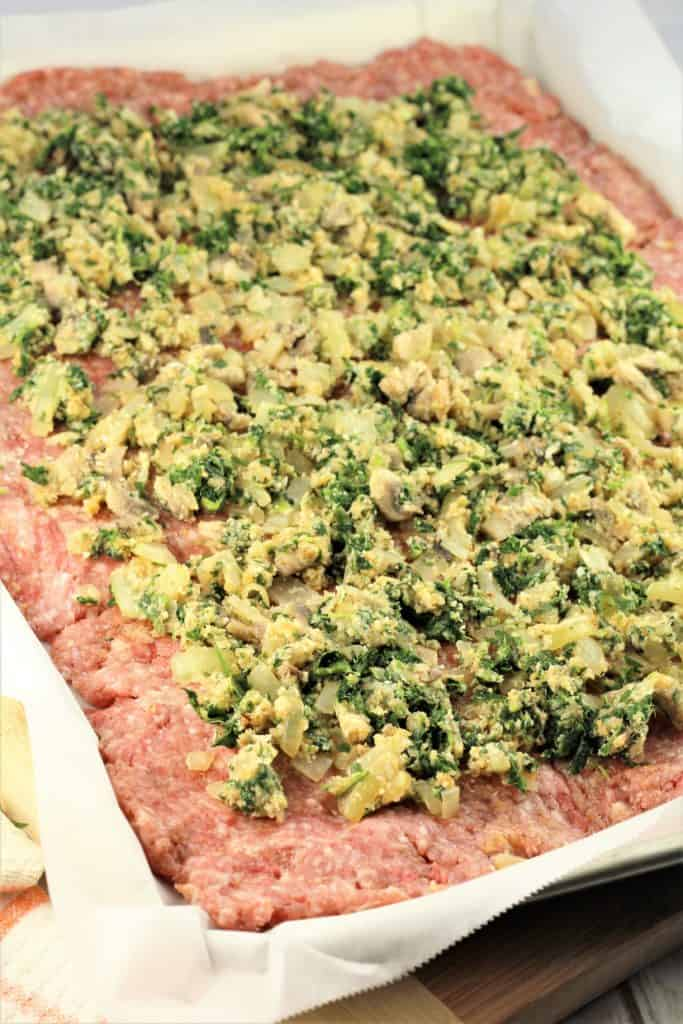 flattened ground meat on sheet pan covered with spinach mushroom mixture