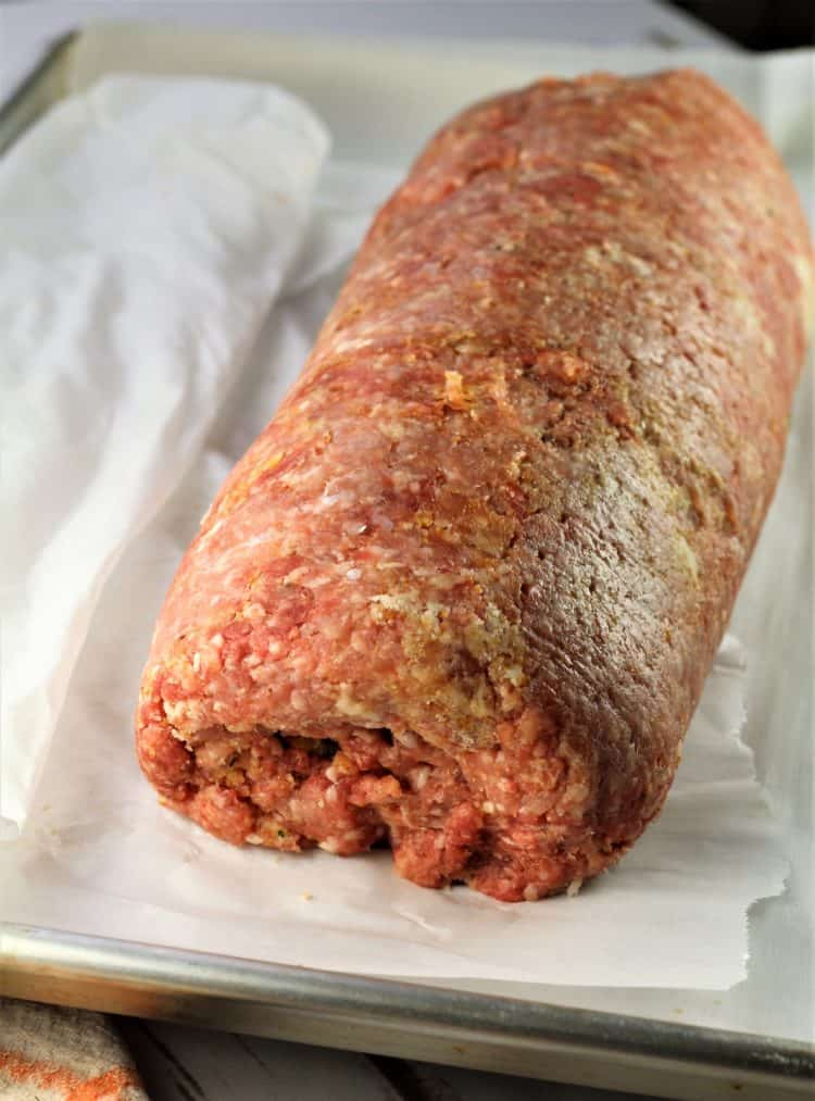 rolled pinwheel meatloaf on parchment paper on baking sheet