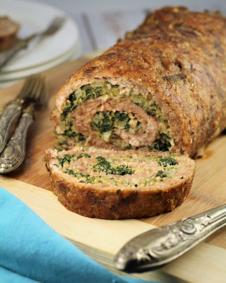 sliced Spinach and Mushroom Filled Pinwheel Meatloaf on wooden board with utensils