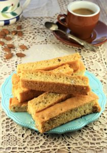 Sheet Pan Almond Biscotti on blue bowl with coffee cup