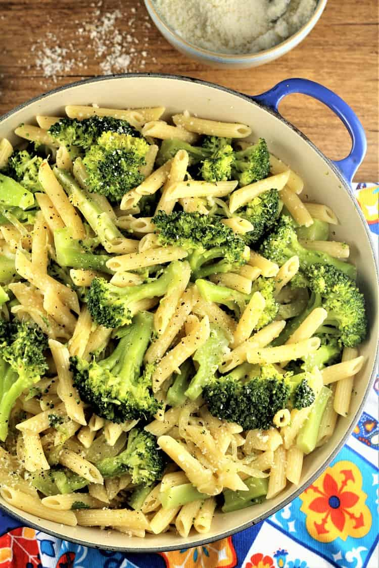 overhead view of blue pan filled with pasta and broccoli and cheese bowl behind it