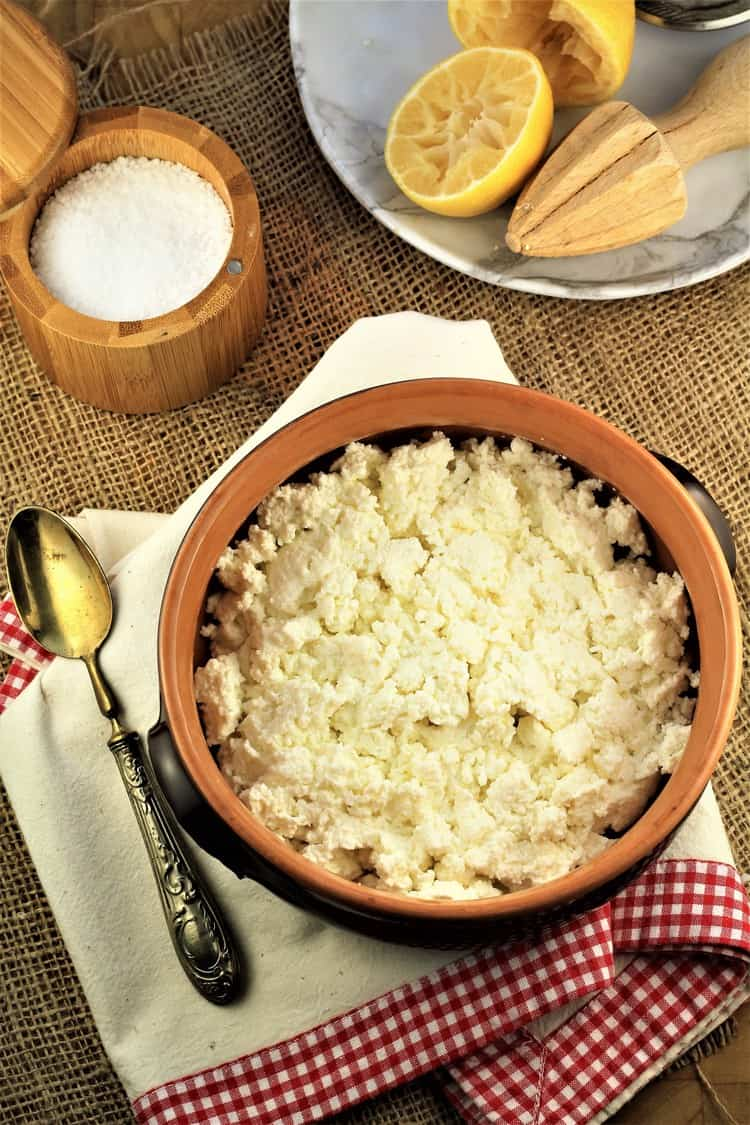 bowl of fresh ricotta curds on dish towel with spoon, halved lemon and container of salt