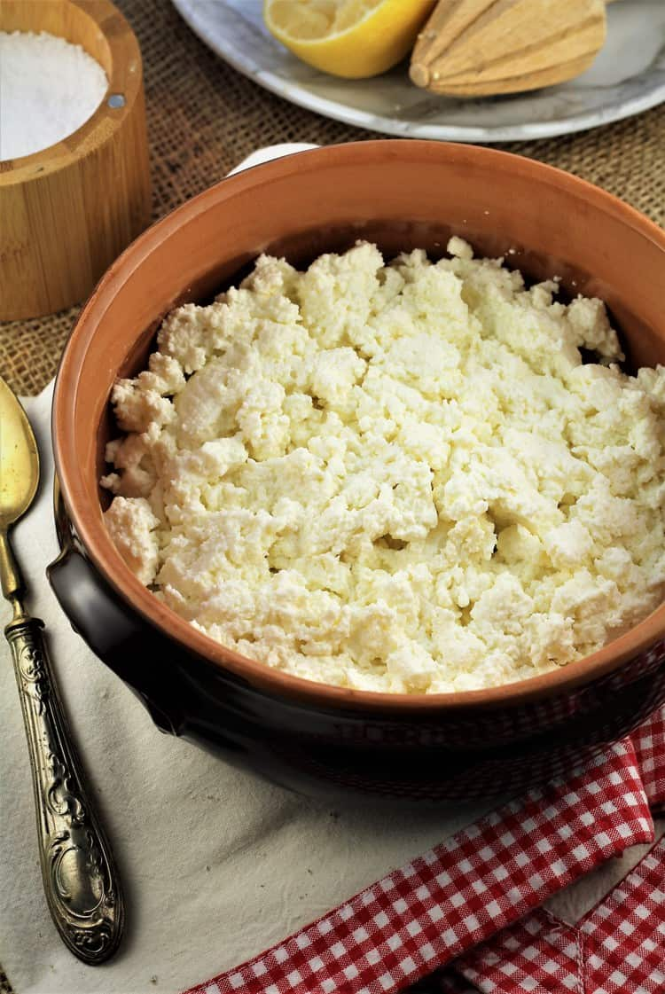 bowl filled with fresh ricotta curds on dish towel with spoon, halved juiced lemon and salt