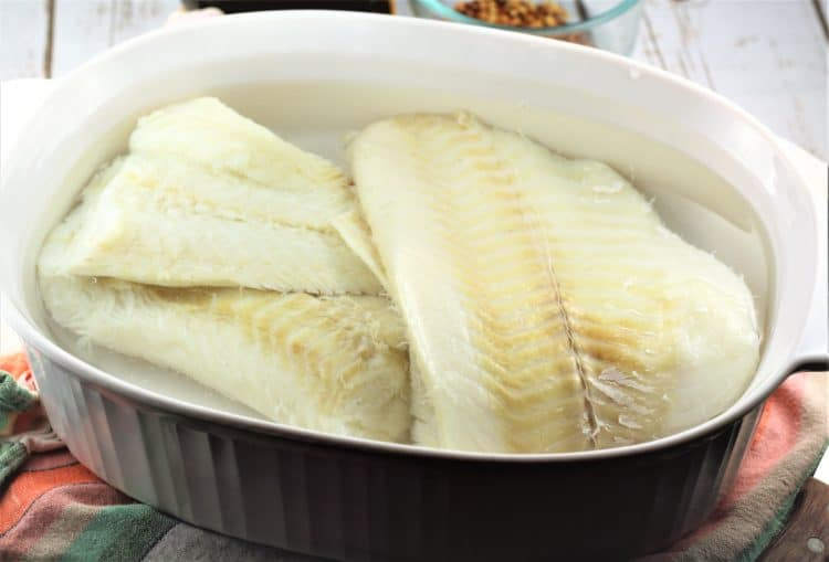 soaking salt cod in water in a white casserole dish