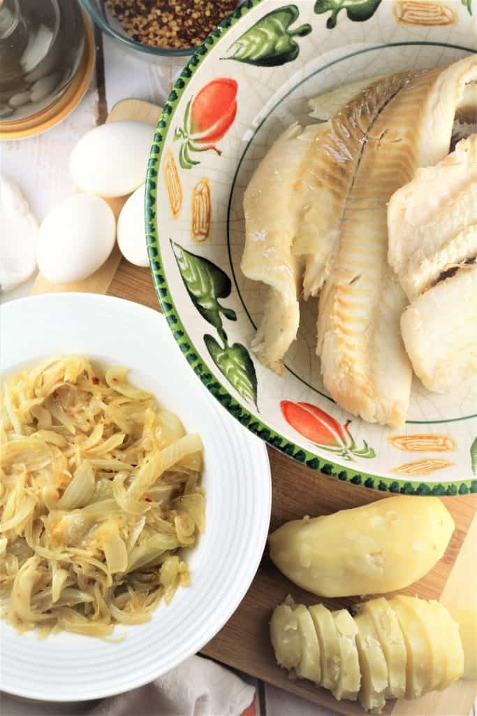 large bowl with salt cod, bowl with sauted onions, sliced boiled potatoes and eggs