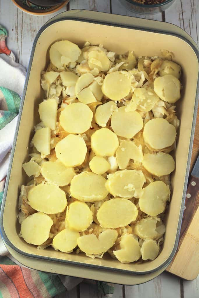 rectangular casserole dish covered with sliced potatoes
