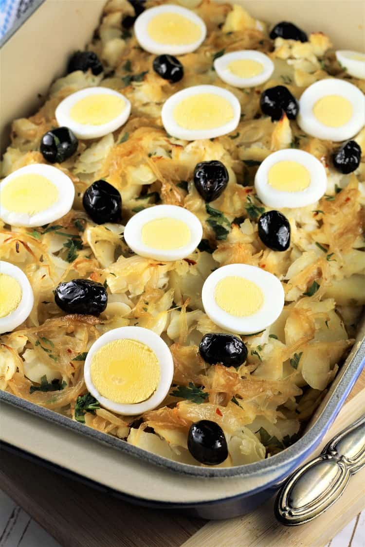 salt cod and potato casserole topped with hard boiled egg slices and black olives