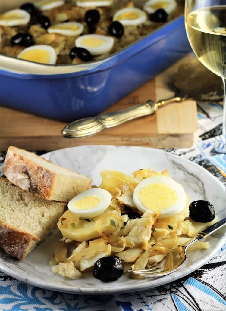 plate with salt cod, potatoes topped with sliced hard boiled eggs, olives and bread slices with glass of white wine