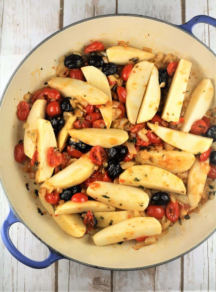 large blue skillet with potato wedges, tomatoes, black olives and onions