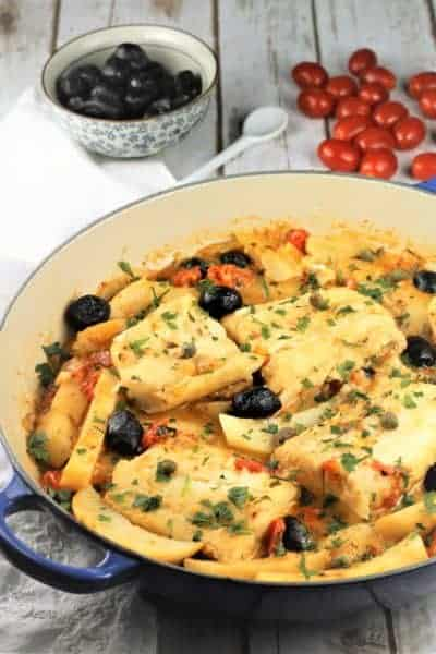blue skillet with salt cod, potatoes, tomatoes and black olives