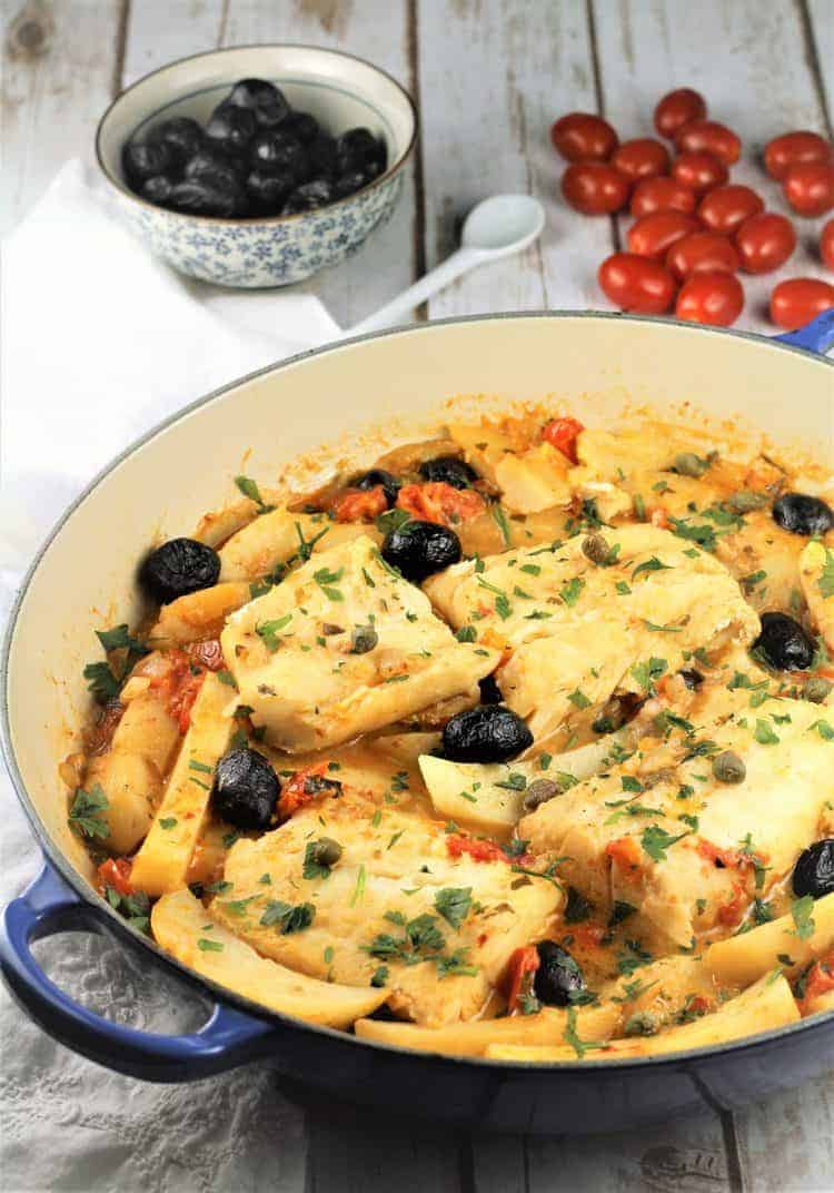 blue skillet with salt cod pieces surrounded by olives and black olives