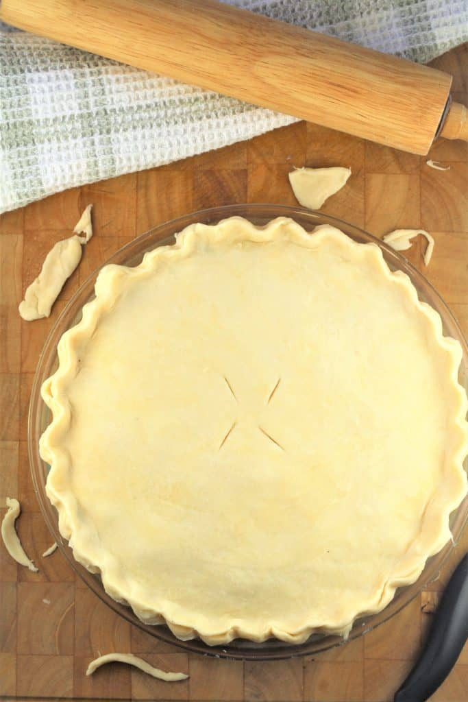 placing top crust on meat pie and crimping edges