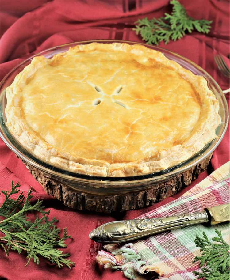 tourtière on a red cloth with serving knife