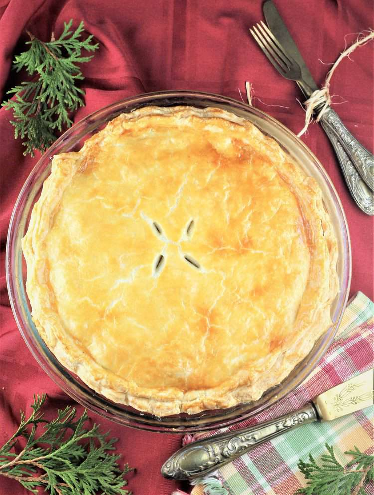 overhead view of tourtière with greenery and utensils on side