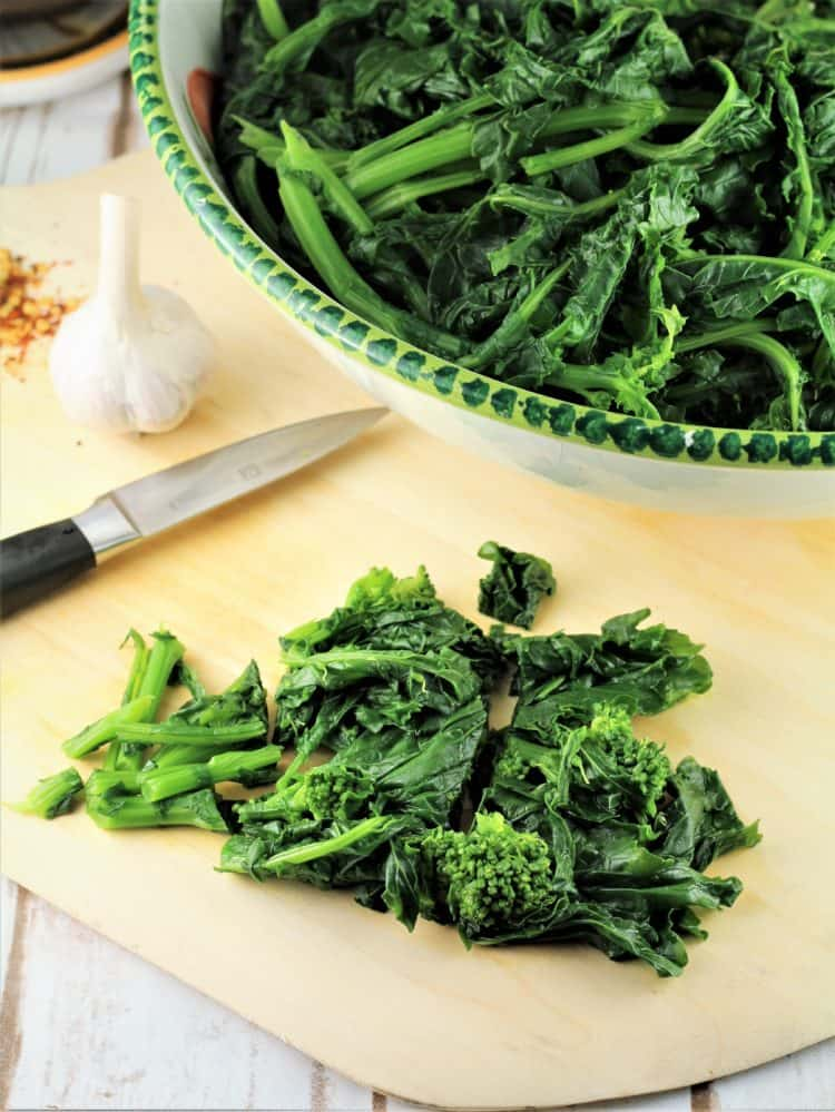 chopped rapini on cutting board with knife, garlic and red pepper flakes