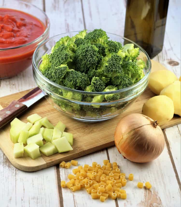 bowl with broccoli on cutting board with broccoli stems, onion, pasta, potatoes and bowl of tomato sauce