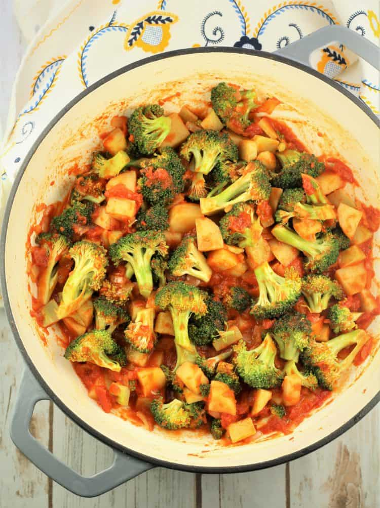large skillet with broccoli pieces in tomato sauce