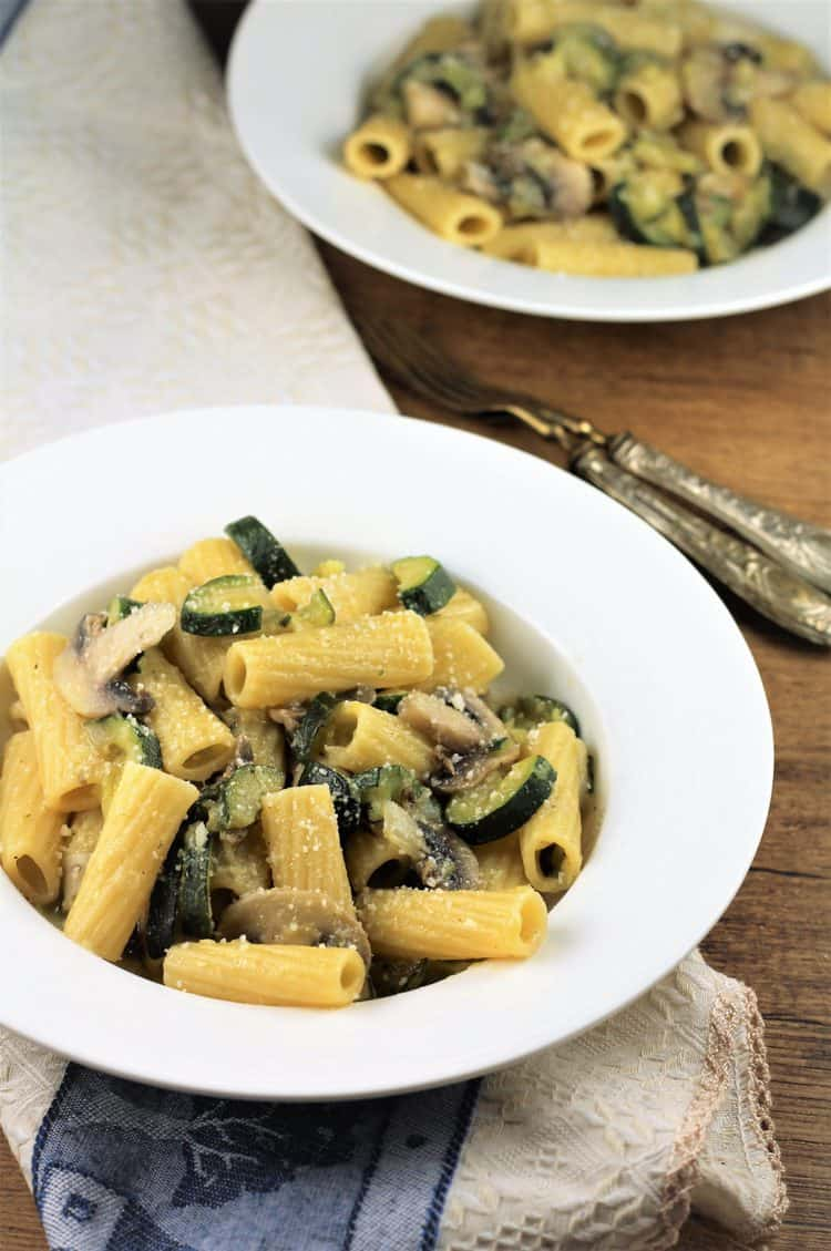 two white plates filled with zucchini mushroom pasta