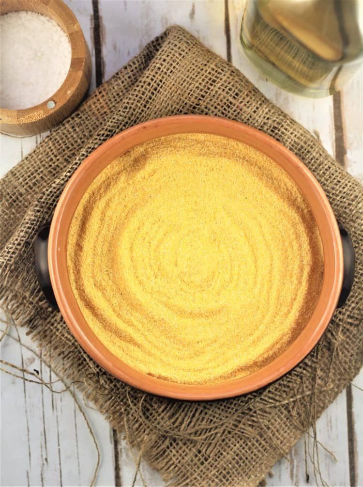 ceramic bowl filled with cornmeal with salt bowl and olive oil bottle behind it