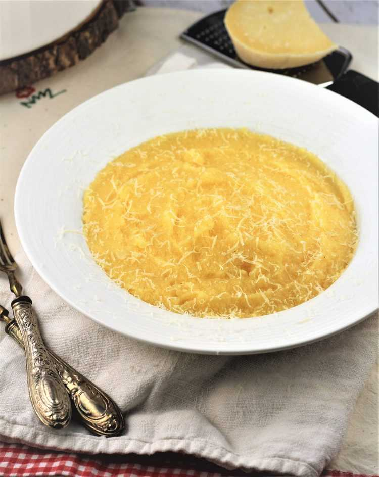 white bowl filled with creamy polenta with utensils and cheese with grater