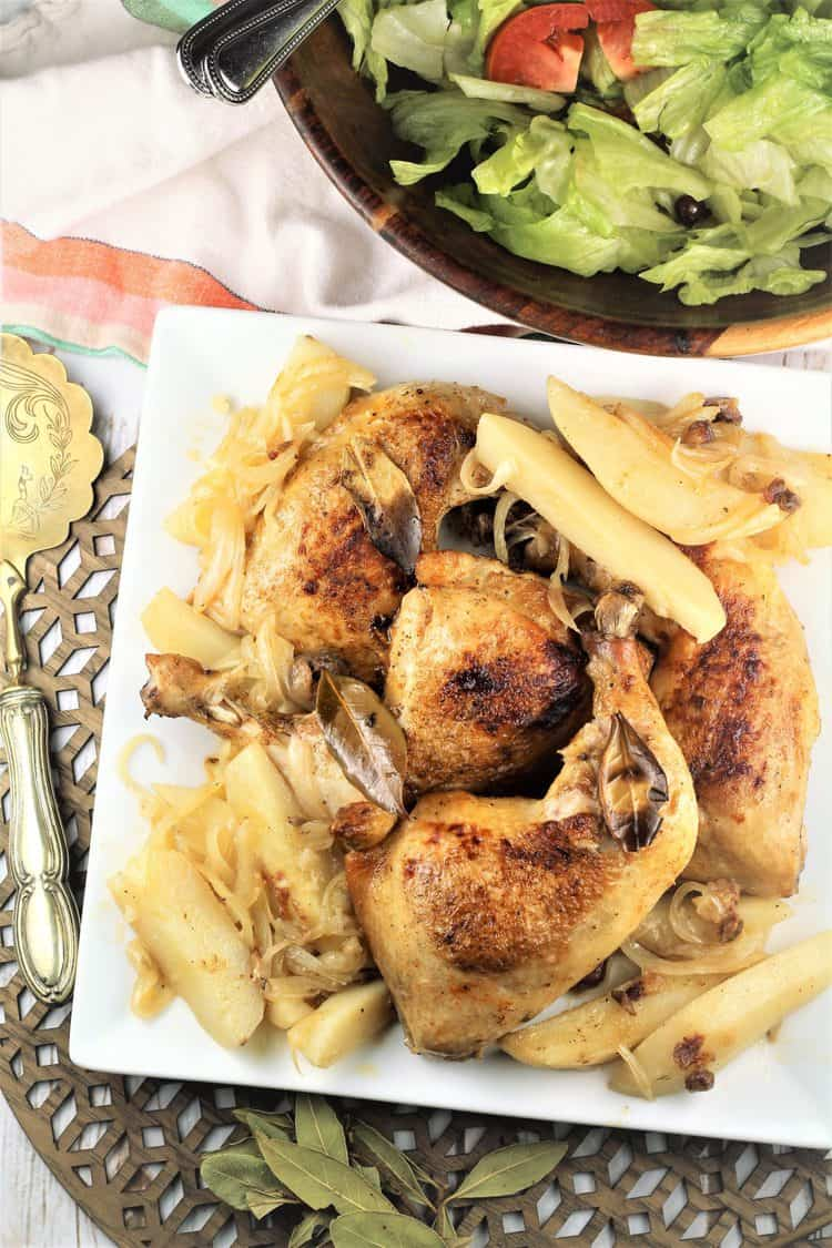 white square plate with roast chicken and potatoes with salad in background
