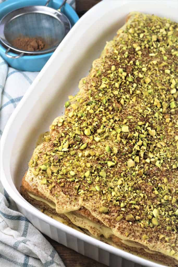 overhead view of pistachio tiramisu with cocoa and sifter on side