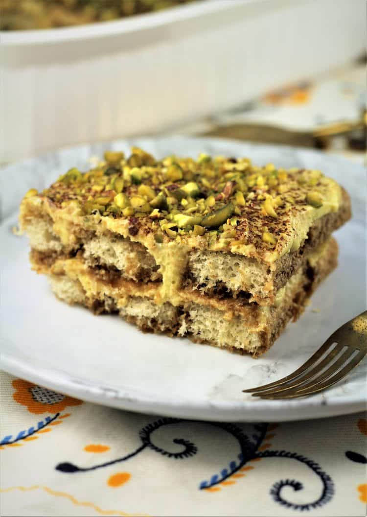 piece of pistachio tiramisu on white plate with fork