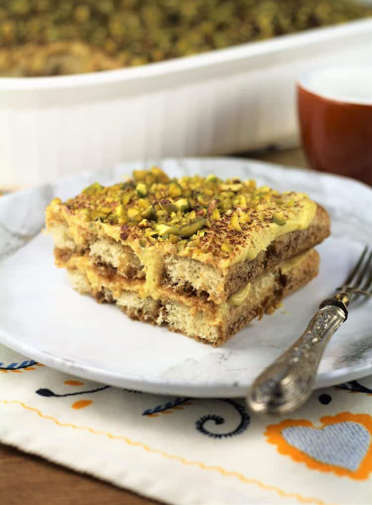 slice of pistachio tiramisu on white plate with fork