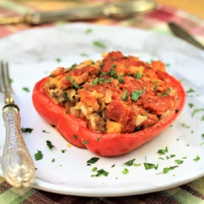 stuffed red pepper half on white plate sprinkled with parsley