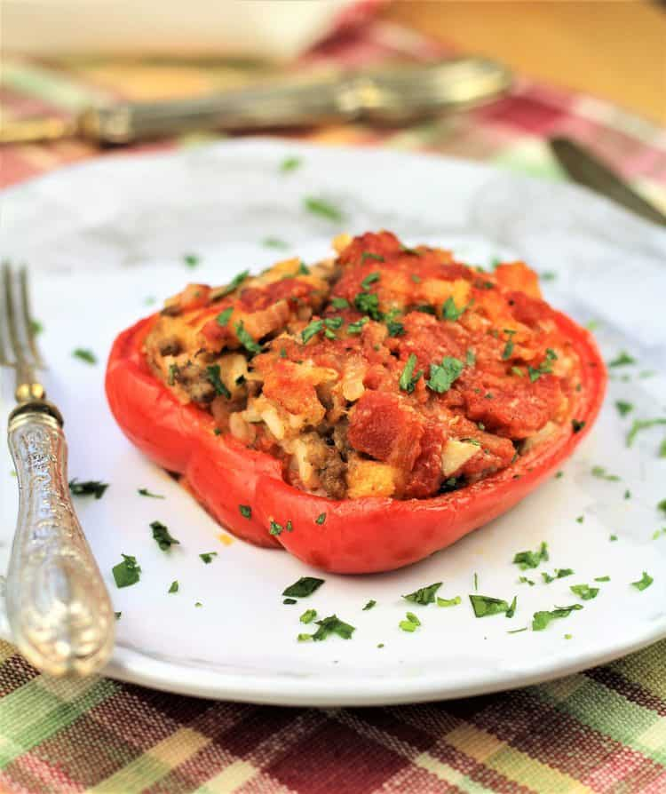 stuffed red pepper half on white plate sprinkled with parsley and fork on side