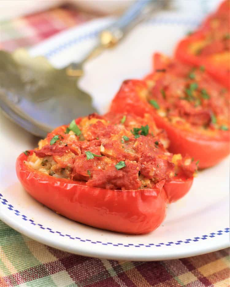 white plate with 3 stuffed red peppers and serving spoon