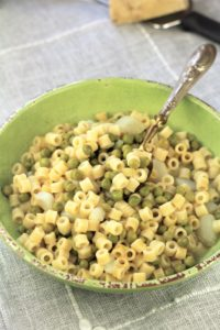 green bowl with pasta and peas and spoon