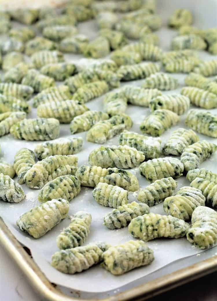 raw spinach gnocchi on a baking sheet