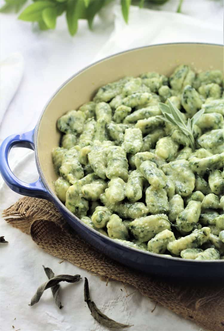 blue skillet filled with spinach gnocchi with butter sage sauce