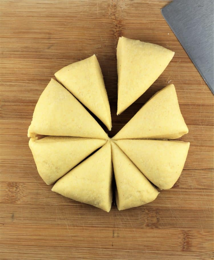 ball of semolina dough cut into 8 wedges on wood baord