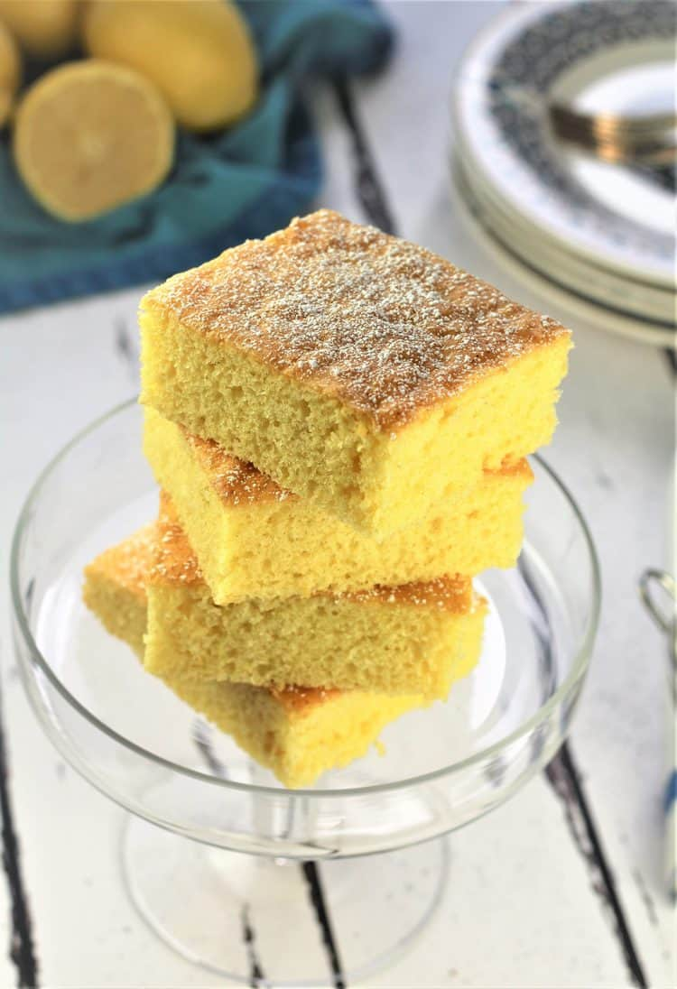 stacked lemon cake squares on glass footed plate with lemons in background
